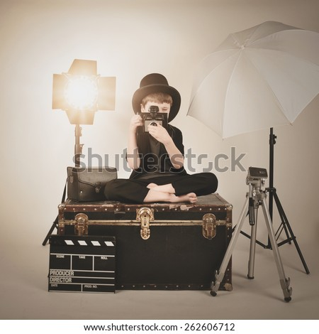 A retro child is holding a vintage camera and focusing with various photography lighting equipment for a director or film concept. - stock photo