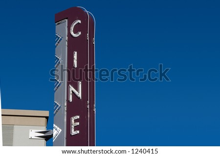 "A retro ""Cine� sign, outside of a movie theater."