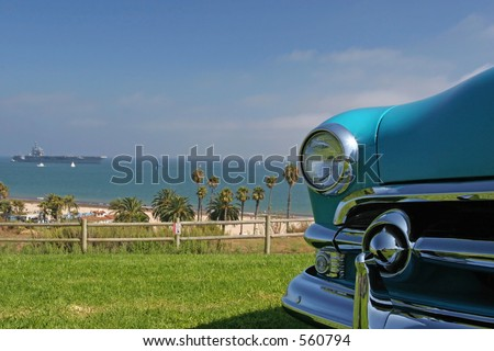 A retro classic car with the USS Ronald Reagan in the background in Santa Barbara, California. - stock photo