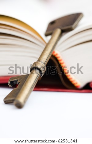 a retro golden key on thick hard cover book.  Macro with extremely shallow depth of field - stock photo
