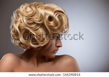 A retro photo of a sensual blond woman with a curly vintage hairstyle. - stock photo