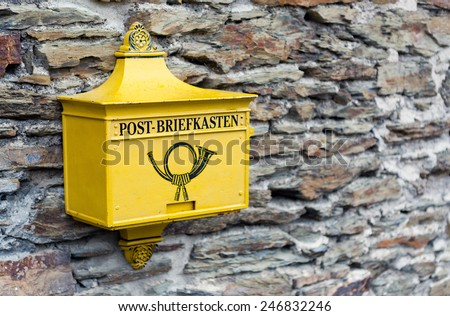 A retro postbox in yellow color in Marksburg, Germany. - stock photo