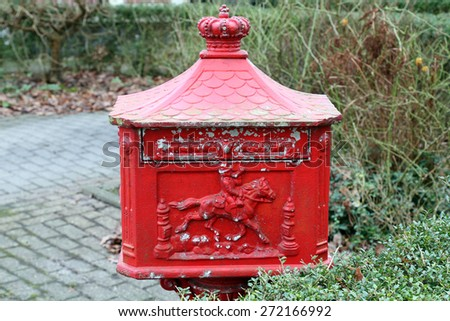 A retro red mailbox in a garden. Little bit damaged giving it a grungy old look. - stock photo