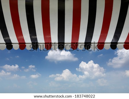 A retro stripe cafe canopy awning against a blue cloudy sky.  - stock photo