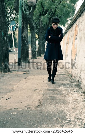 A retro styled girl walking down a rotten street along a graffiti sprayed wall in a urban environment.