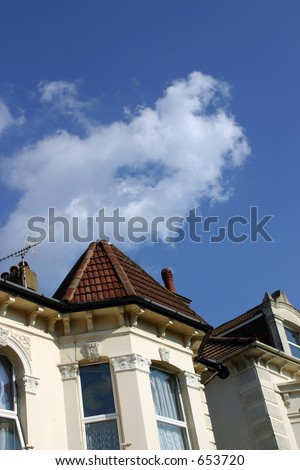 A rich, blue sky above some houses. - stock photo