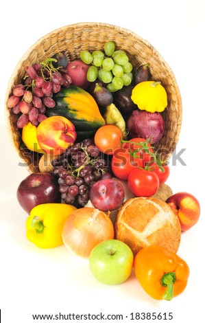 A rich bounty of autumn harvest foods spilling from a basket - stock photo