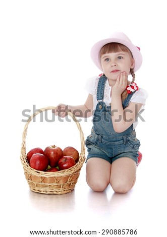 A rich harvest of apples lies in the basket which keeps little girl - isolated on white background - stock photo