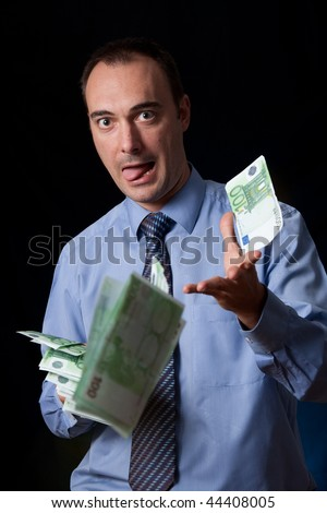 A rich man is throwing away a wad of money. Disdainful expression.  Conceptual image for wealthy lifestyle, success, spending money, and so on. - stock photo