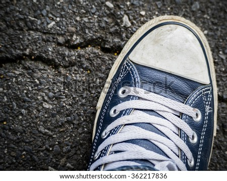 A right foot in sneaker shoes standing on the asphalt road.  (Top view photo in vintage style) | Start off on the right foot | Make a good beginning | establish good-relations | - stock photo