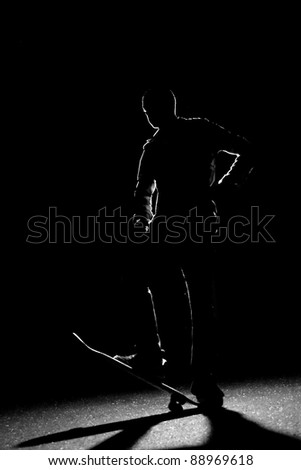 A rim lit skateboarder guy posing under dramatic back lighting with his skateboard flipped up in the front. - stock photo