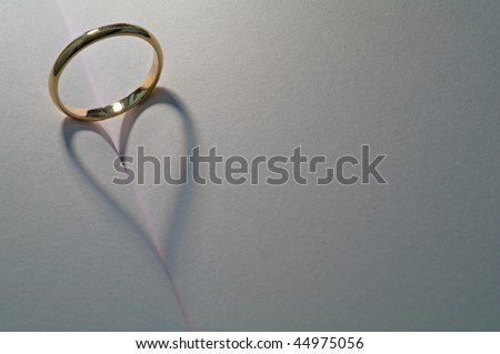 A ring casting a heart shadow onto a book - stock photo