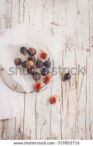 A ripe juicy fresh figs on a old vintage white container with linen cloth and plate of cream cheese  in a rustic kitchen from above. Rustic style. See more recipe image. - stock photo