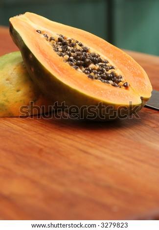 A ripe papaya cut in half on a wooden chop block. - stock photo