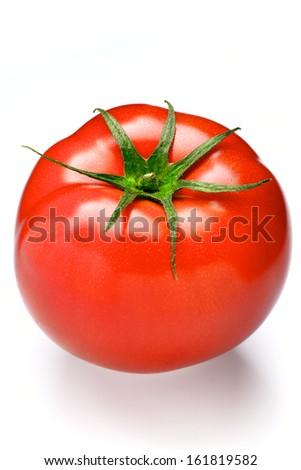 A ripe red tomato off of the vine. - stock photo