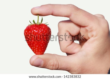 A ripe strawberry presented between two fingers against a flat white background