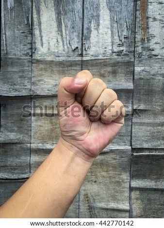 A rising fist with old wood background. Fist for fight, revolution. Fight for poverty and justice democratization or equality or something.