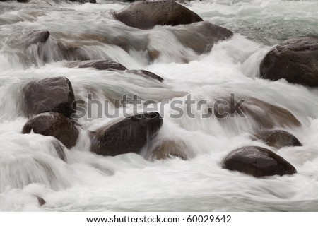 A river blured and looking peaceful rolling over rocks in nature. - stock photo