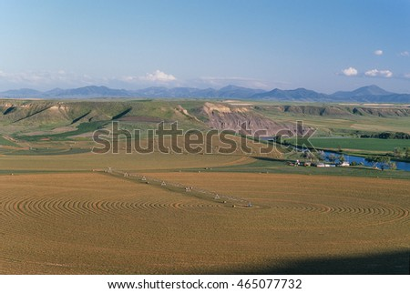 A river bottom farm with huge circular hay fields with river breaks and mountain range in the far distance and a big clear blue sky. Gorgeous late evening summer day near sundown.
