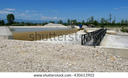 a river in Kossovo and in the background a truck and an excavator. - stock photo