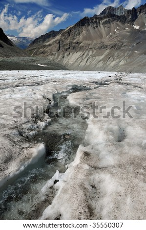 a river running over the surface of a glacier, caused by melted ice. Global warming is causing the worlds glaciers to melt - stock photo