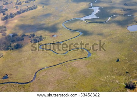 A river twists and bends through the green bushlands of the Okavango Delta, Botswana.
