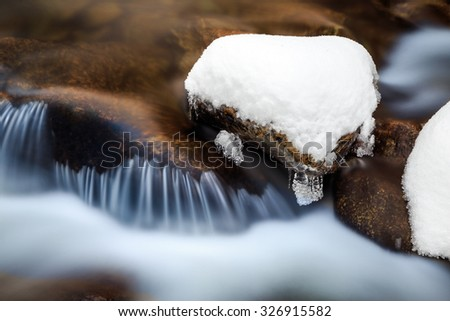 a river with rock in snow and icicles, russian nature - stock photo