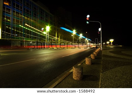 A road at night in Tel Aviv with colorful light trails from passing traffic - stock photo