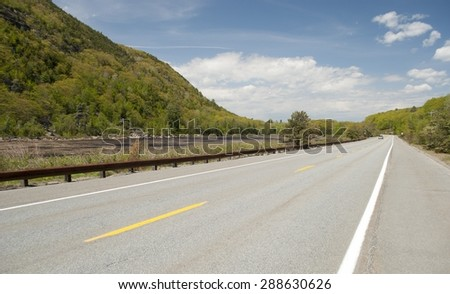 A road leading cars by a scenic pond, and mountainside, in Maine. - stock photo