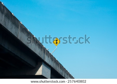 A road Merge Sign on expressway against blue sky - stock photo