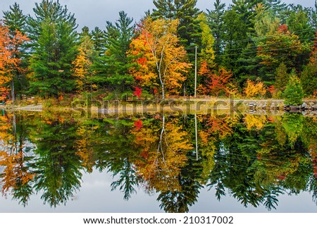 A road running by a lake surrounded by colorful trees in the fall.  - stock photo