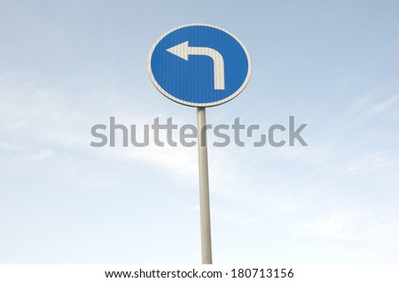 a road sign indicating a movement on the left in the background of the blue sky