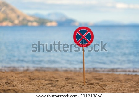 A road sign installed on a sandy beach - stock photo