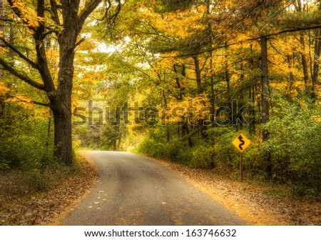 A road sign says Curves Ahead on a quiet country road in the fall - stock photo
