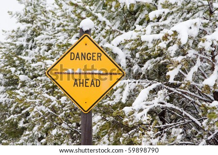 A road sign warns against some undefined danger on a snowy day - stock photo