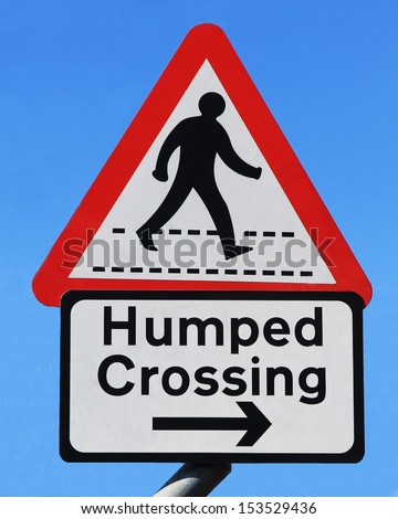 A road sign with a pedestrian crossing symbol and the description of 'humped crossing' - stock photo