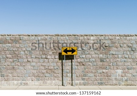 A road sign with double arrows over a brick wall - stock photo