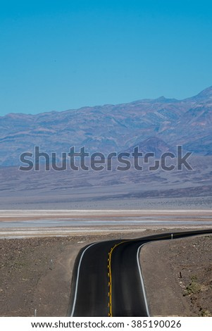 A road to Death Valley along the mountains and salt flats - stock photo
