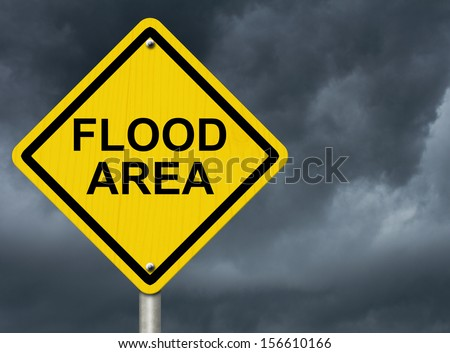 A road warning sign against a stormy sky with words Flood Area, Flood Warning - stock photo