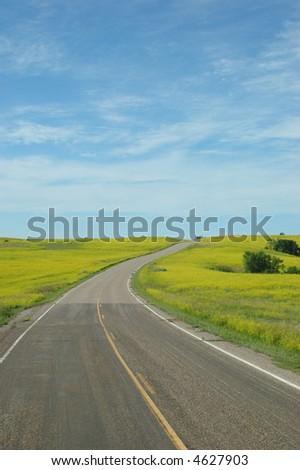 A road winding through North Dakota's wide open space. - stock photo