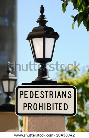 A roadsign - Pedestrians prohibited with a blue sky, building, lamp and trees in the background