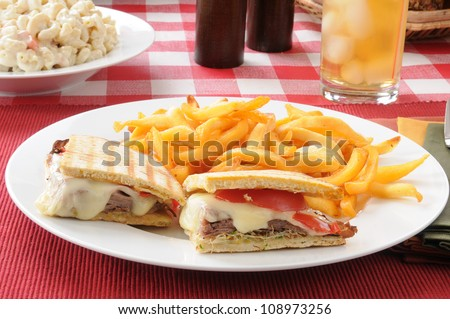 A roast beef panini with fries and macaroni salad
