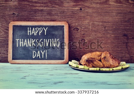 a roast turkey in a tray with vegetables and a chalkboard with the text happy thanksgiving day written in it on a blue wooden rustic table - stock photo