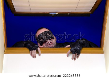 A robber enters the house through the roof window  - stock photo