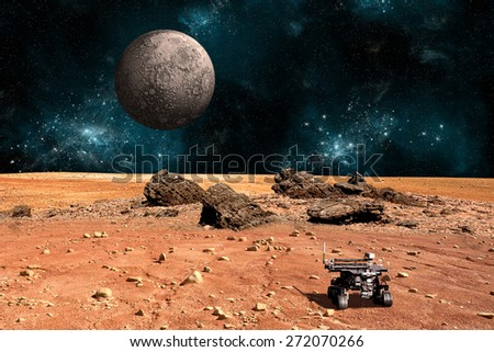 A robotic rover explores the surface of a rocky and barren alien world. A large cratered moon rises over the airless environment.  - Elements of this image furnished by NASA. - stock photo