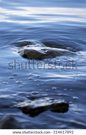 A rock being hit by a soft wave of water on a calme lake. - stock photo