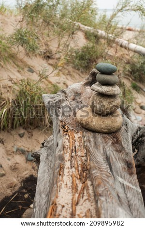 A rock cairn on the end of a log, laying on a sandy beach.  Grand Marais, MI, USA. - stock photo