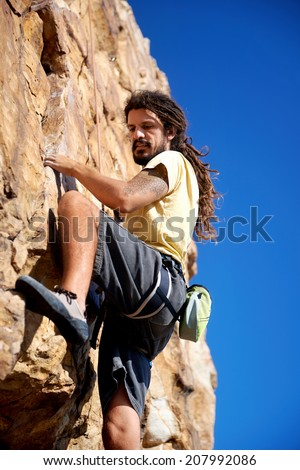 A rock climber finding a foothold on the steep mountain he's climbing - stock photo