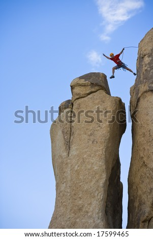 A rock climber leaps across a chasm to a spire in Joshua Tree National Park, California, on a summer afternoon.