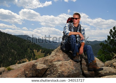 A rock climber sitting above a lake on a mountain